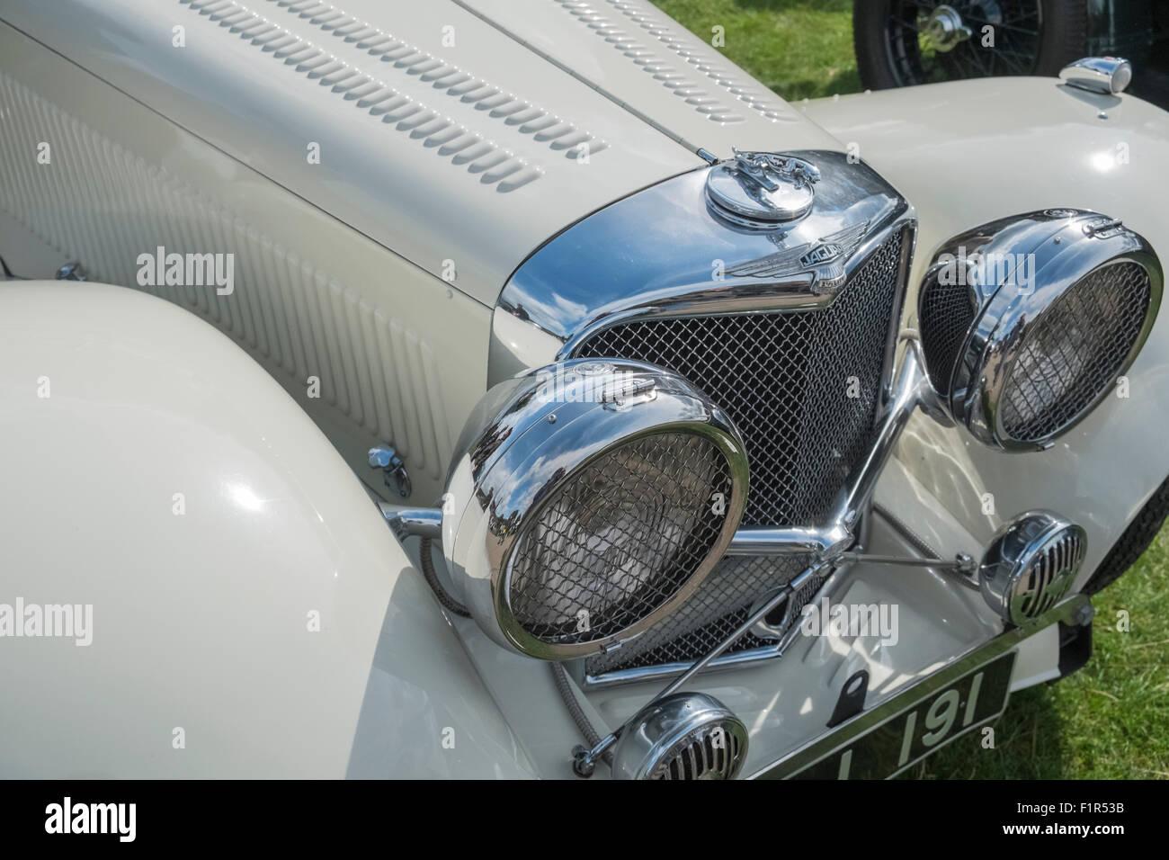 Vintage classic Jaguar car headlamps and radiator grille. - Stock Image