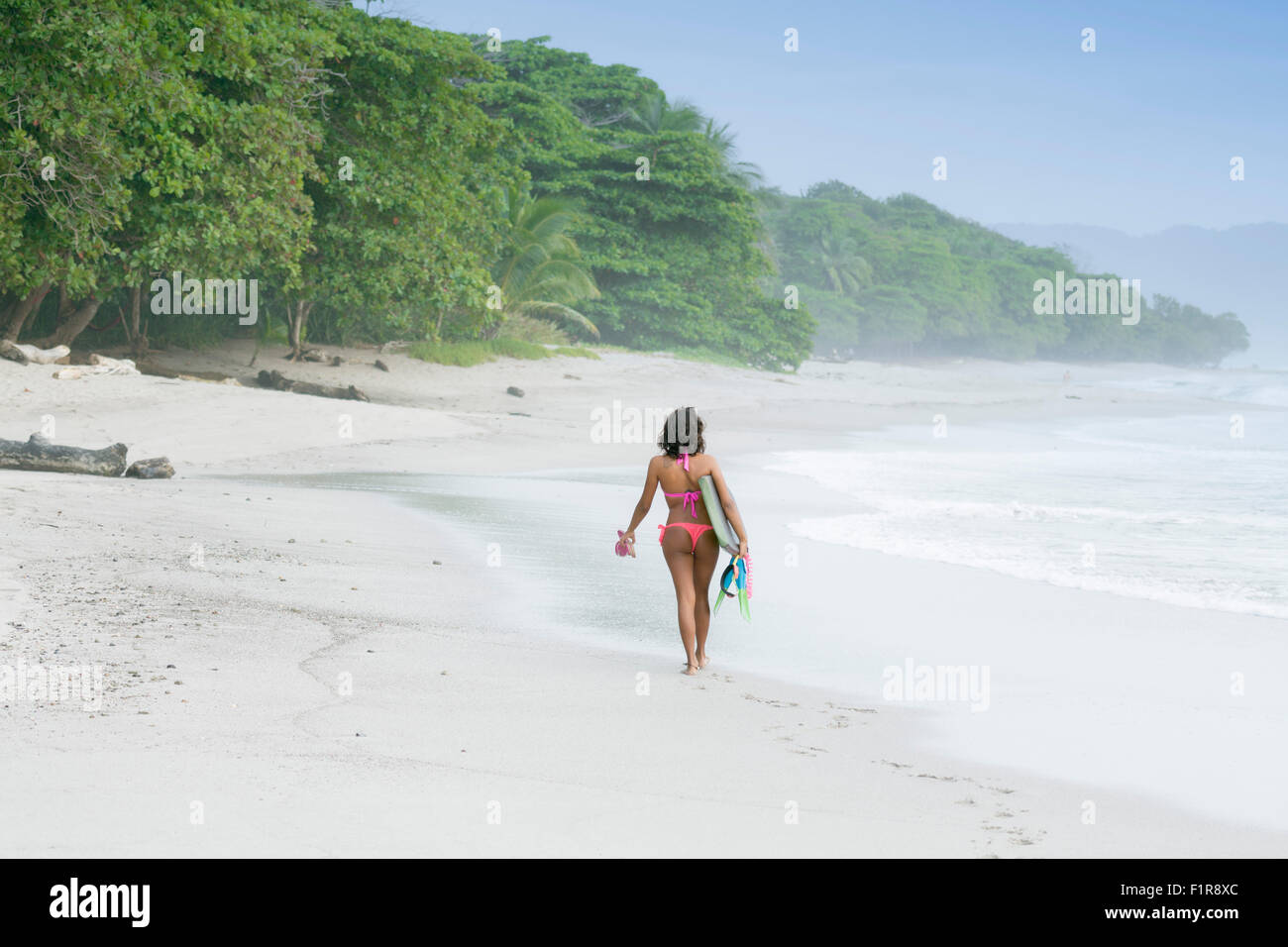 A solo female surfer on a beach in Santa Teresa, Costa Rica, with a body board - Stock Image