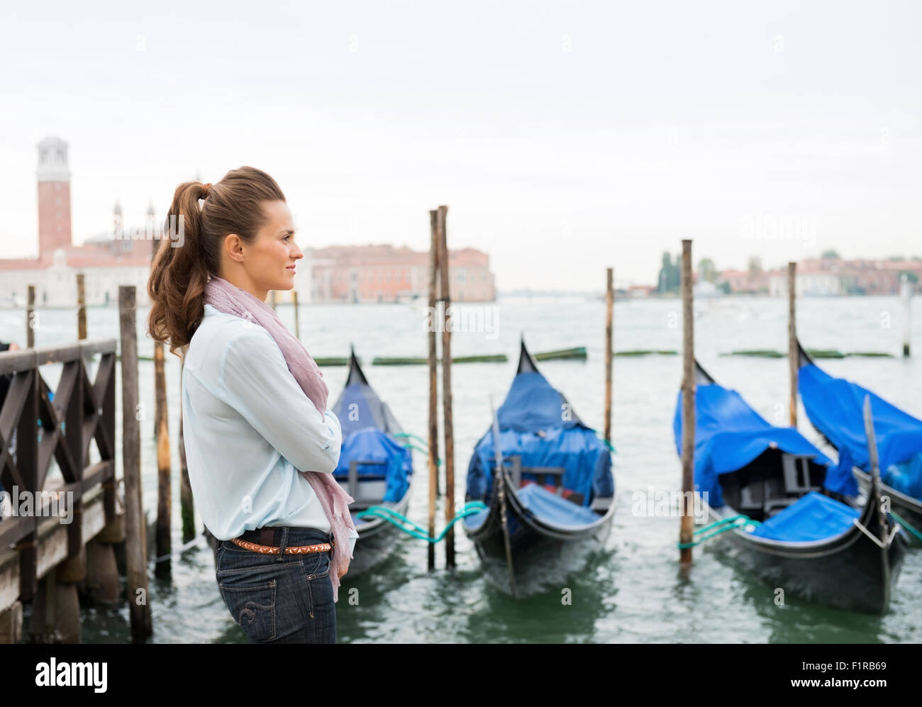 A woman stands, dreaming of times past, listening to the sound of the water lapping against the moored gondolas. - Stock Image