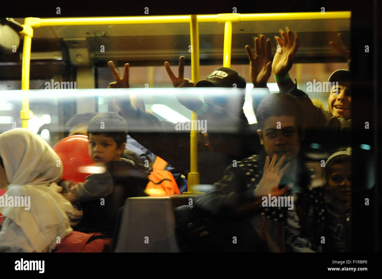 Munich, Germany. 05th Sep, 2015. Refugees wave from a bus which takes them to a reception center after arriving - Stock Image