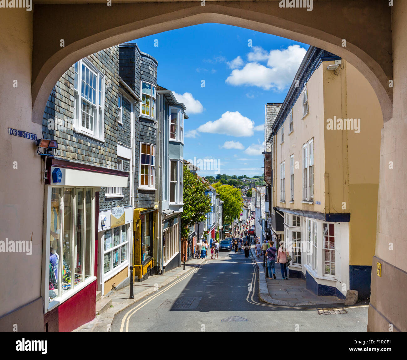 Shops on Fore Street in the town centre viewed from High Street through East Gate arch, Totnes, Devon, England, - Stock Image