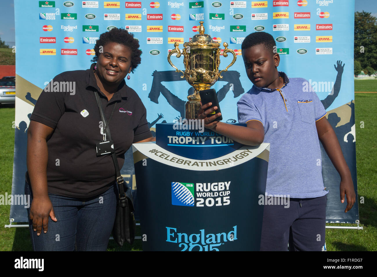 London, UK. 06th September 2015. Selfie moment with the Webb Ellis Cup for Amal whislt being photographed together with his mum Noreen as it was displayed at the East London RFC for the UK and Northern Ireland Rugby World Cup Trophy Tour. Credit: Elsie Kibue / Alamy Live News Stock Photo
