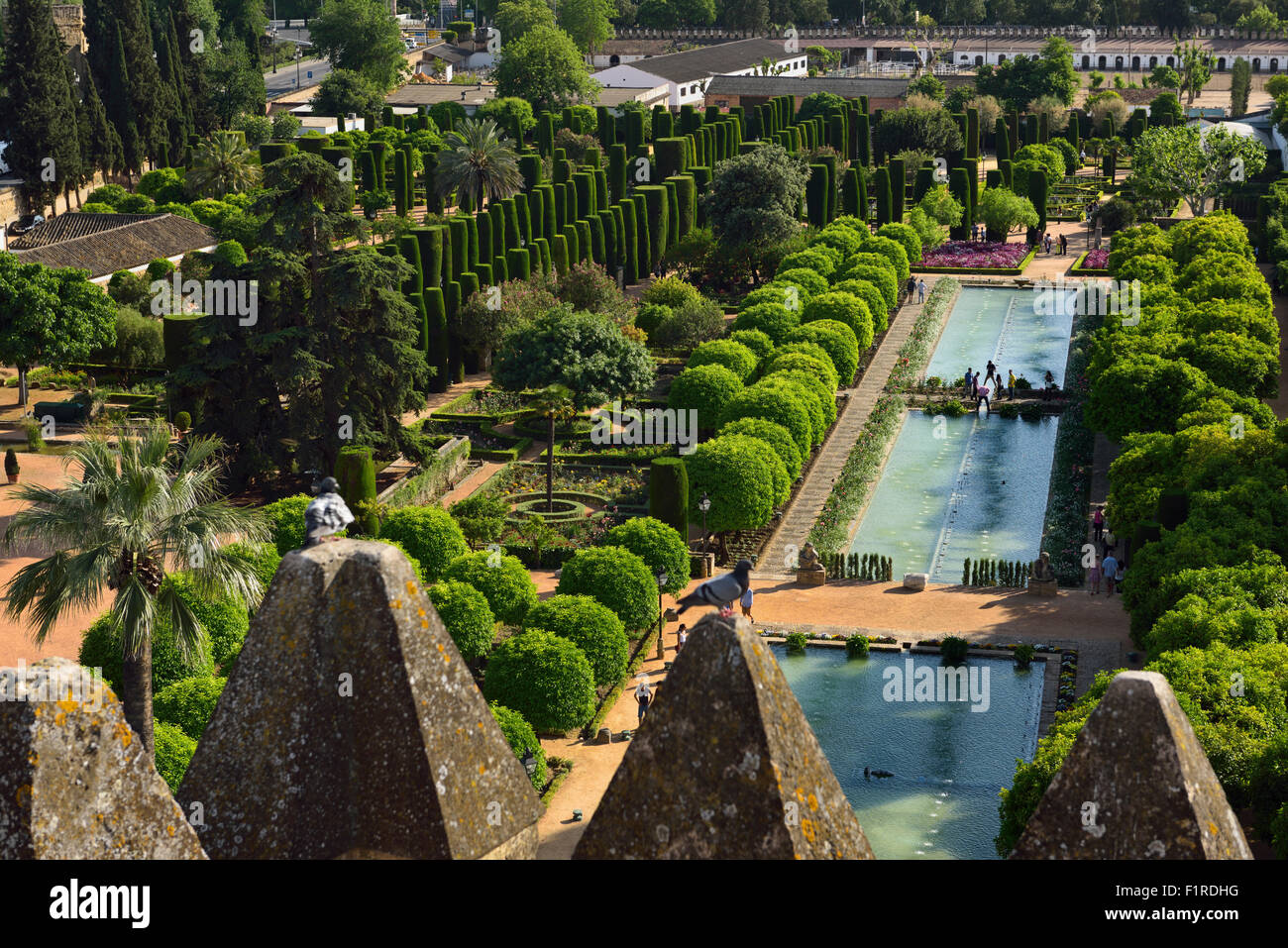 View of gardens and ponds through Tower of Lions merlons Alcazar Cordoba Andalusia Spain - Stock Image