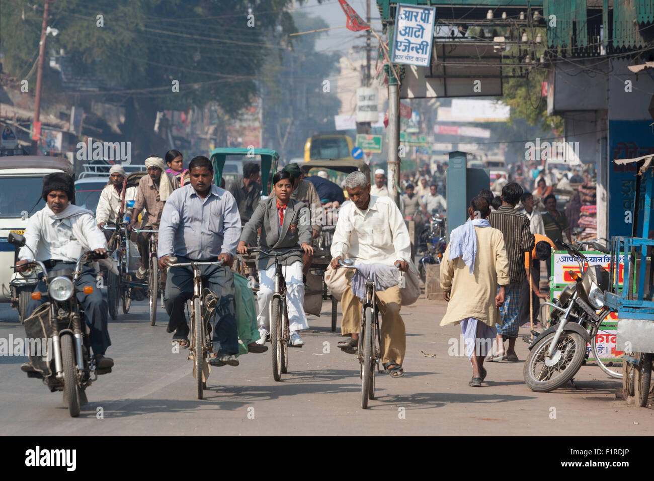 Bicyclists and other traffic on crowded, dusty Raja Bazaar Rd in Varanasi India - Stock Image