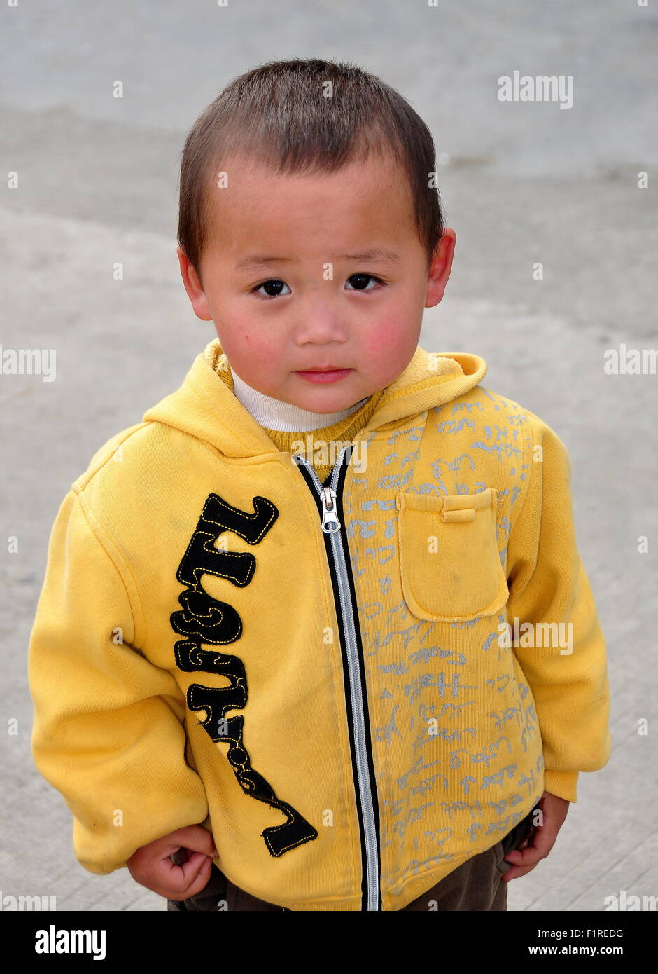Pengzhou, China:  Little Chinese boy wearing a yellow zippered sweater standing on a country road - Stock Image