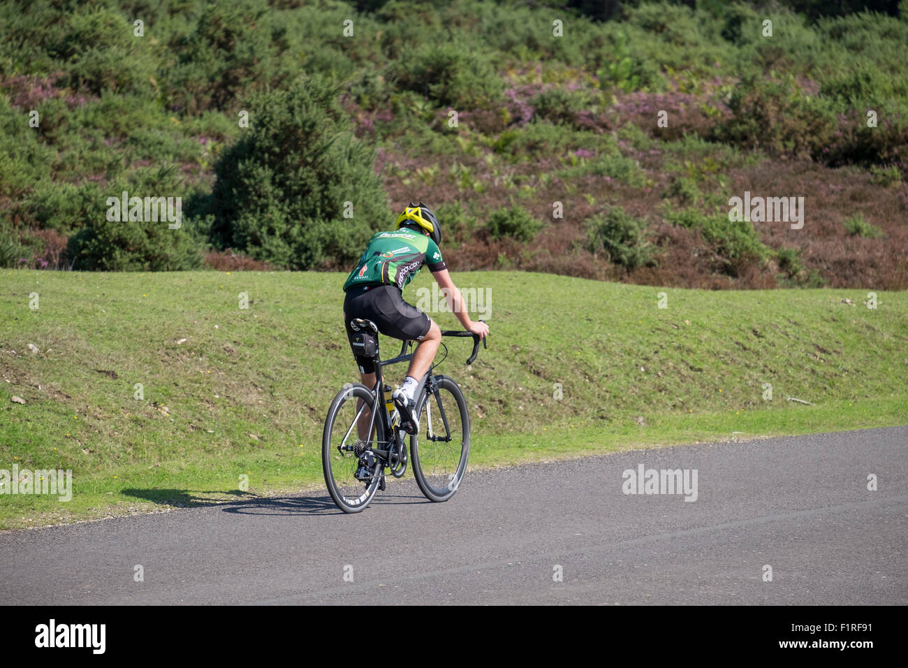 A cyclist shown dressed in the correct attire including safety helmet whilst cycling up a slight incline on a tarmac - Stock Image