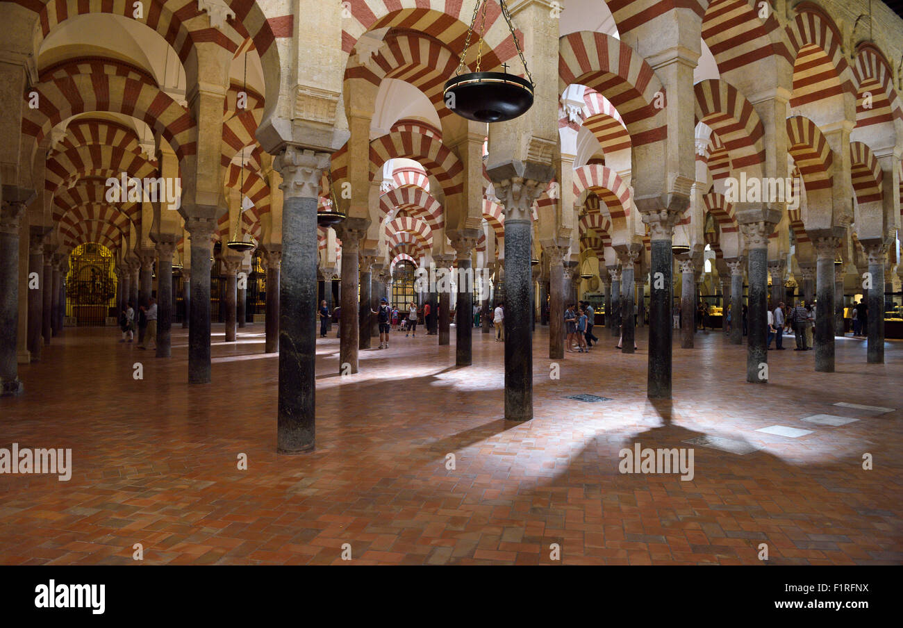 Double red and white arches on ancient Roman columns at the Mosque Prayer Hall in the Cordoba our Lady of the Assumption - Stock Image