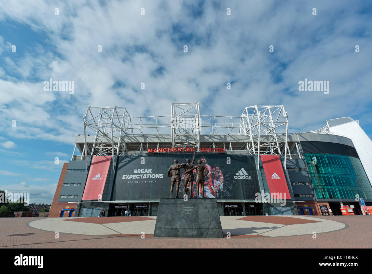 Old Trafford, the stadium of Manchester United Football Club, including the United Trinity (Editorial use only) - Stock Image