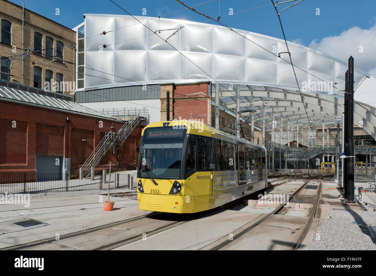 The refurbished Victoria Station in Manchester, as a Metrolink LRT tram emerges - Stock Image