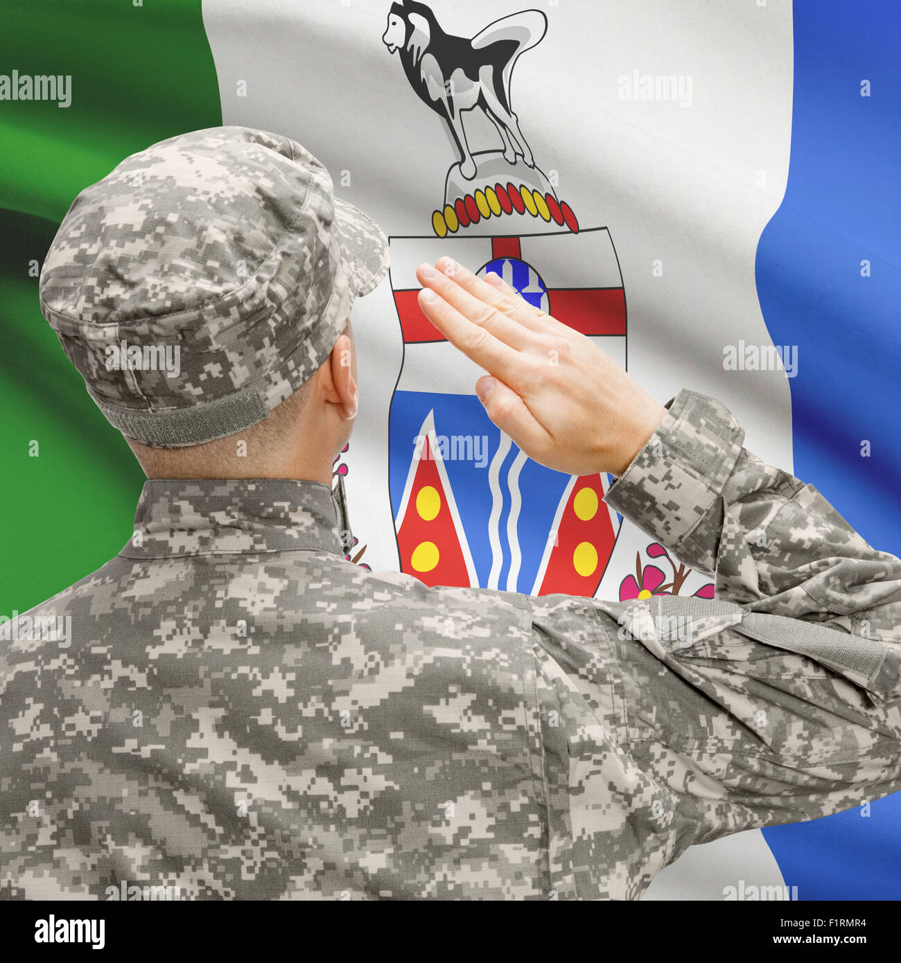 Soldier saluting to Canadial province flag conceptual series - Yukon Stock Photo
