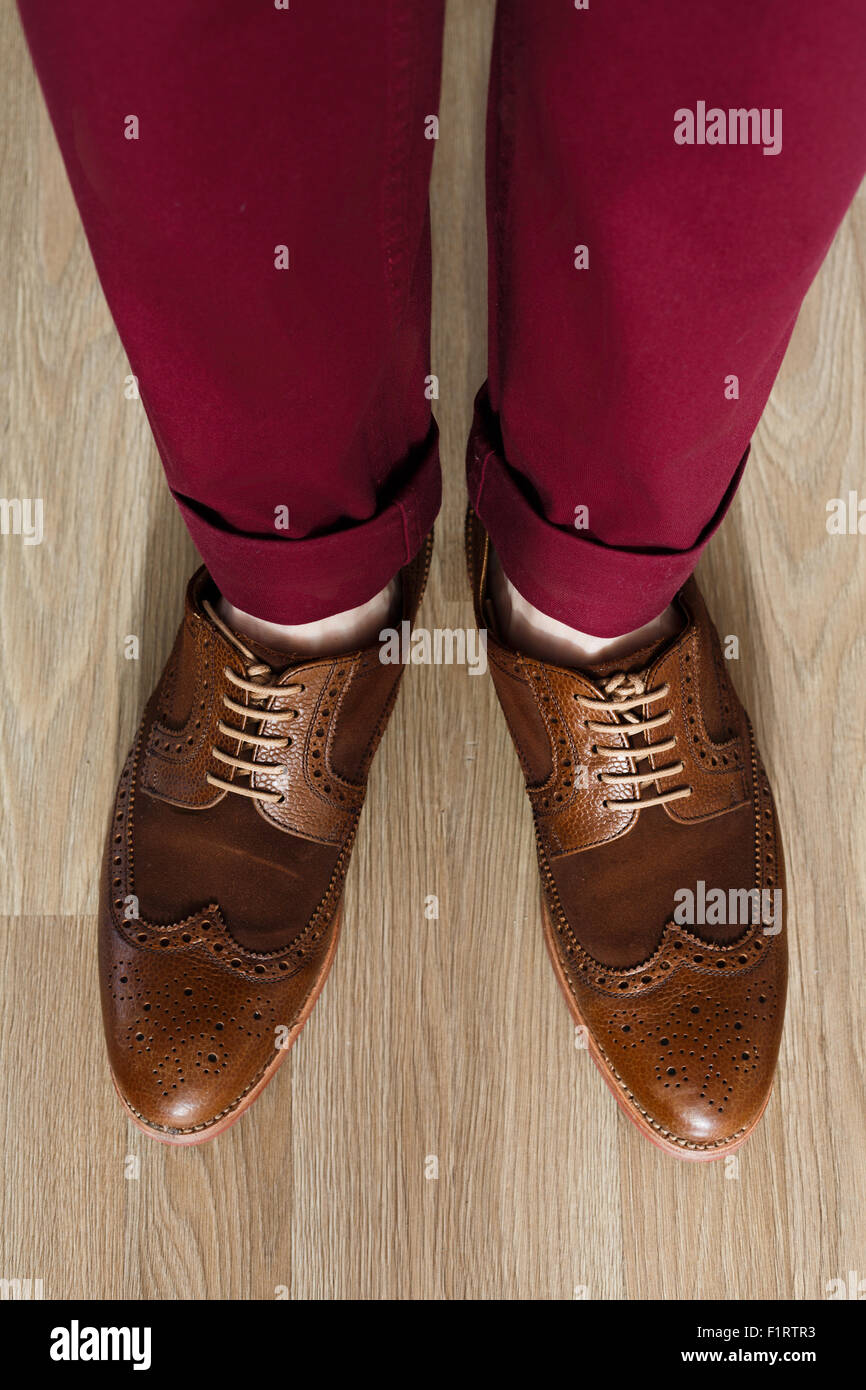 Sockless male legs in two tone suede brogues, Stylish dressed man wearing cushioned pants and wingtips - Stock Image