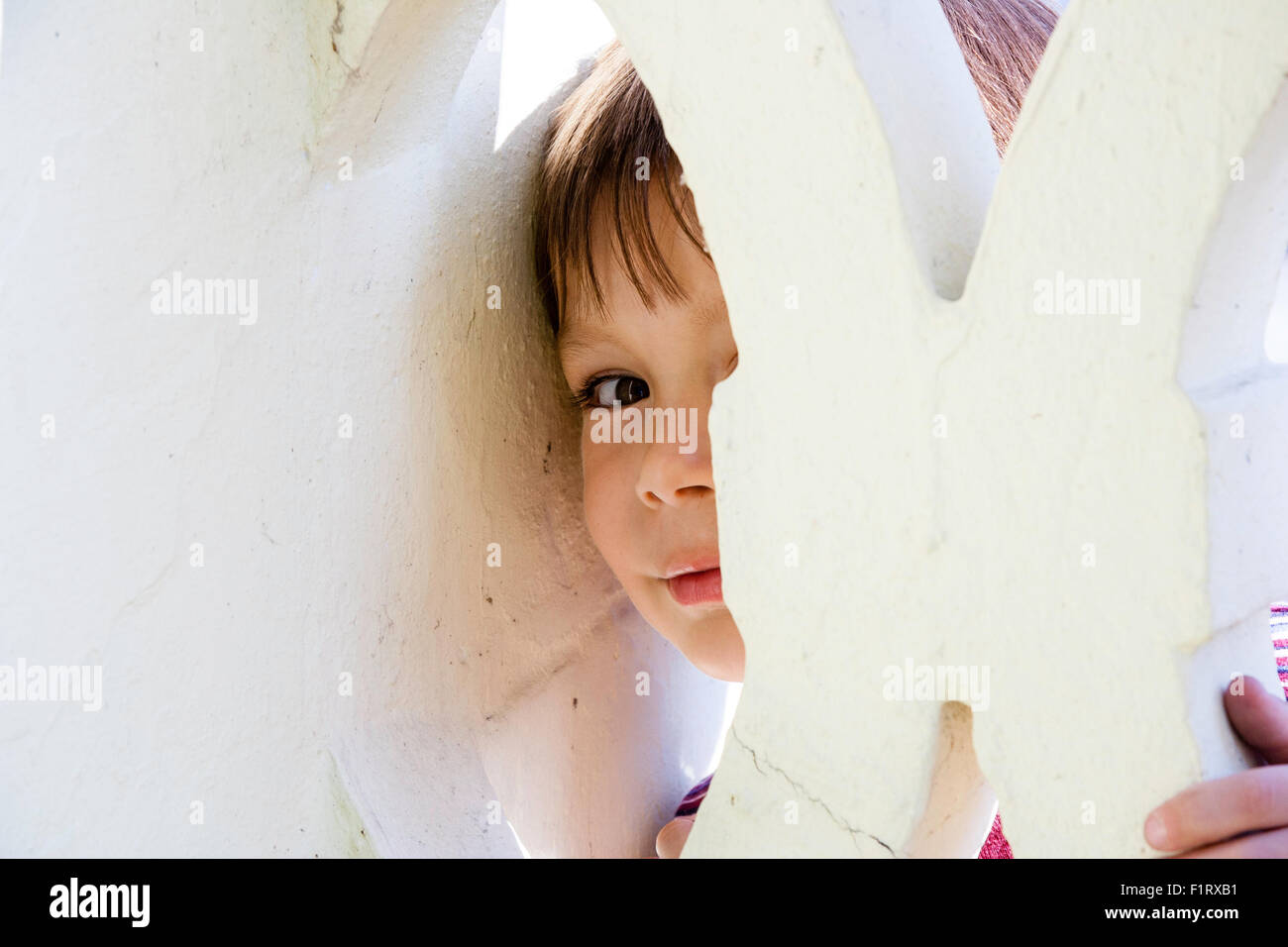 3 to 5 year old Caucasian boy. Outdoor. Half hidden face peeking through gap in wall, looking at viewer. - Stock Image