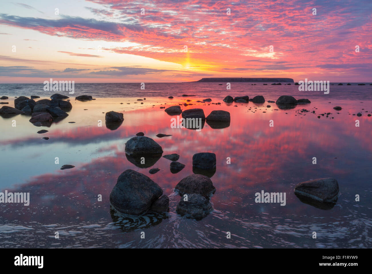 Sunset at the Coast of Eksta on Gotland, Sweden. Warm red colors reflecting in the water and the Islands of Karls - Stock Image