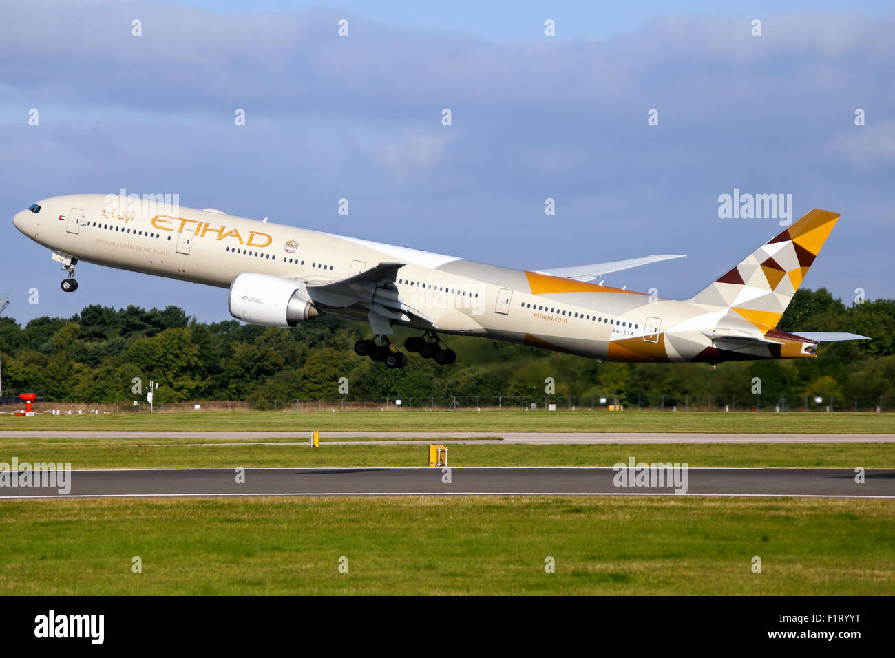 Etihad Airways Boeing 777-300 climbs away from runway 23R at Manchester airport. - Stock Image