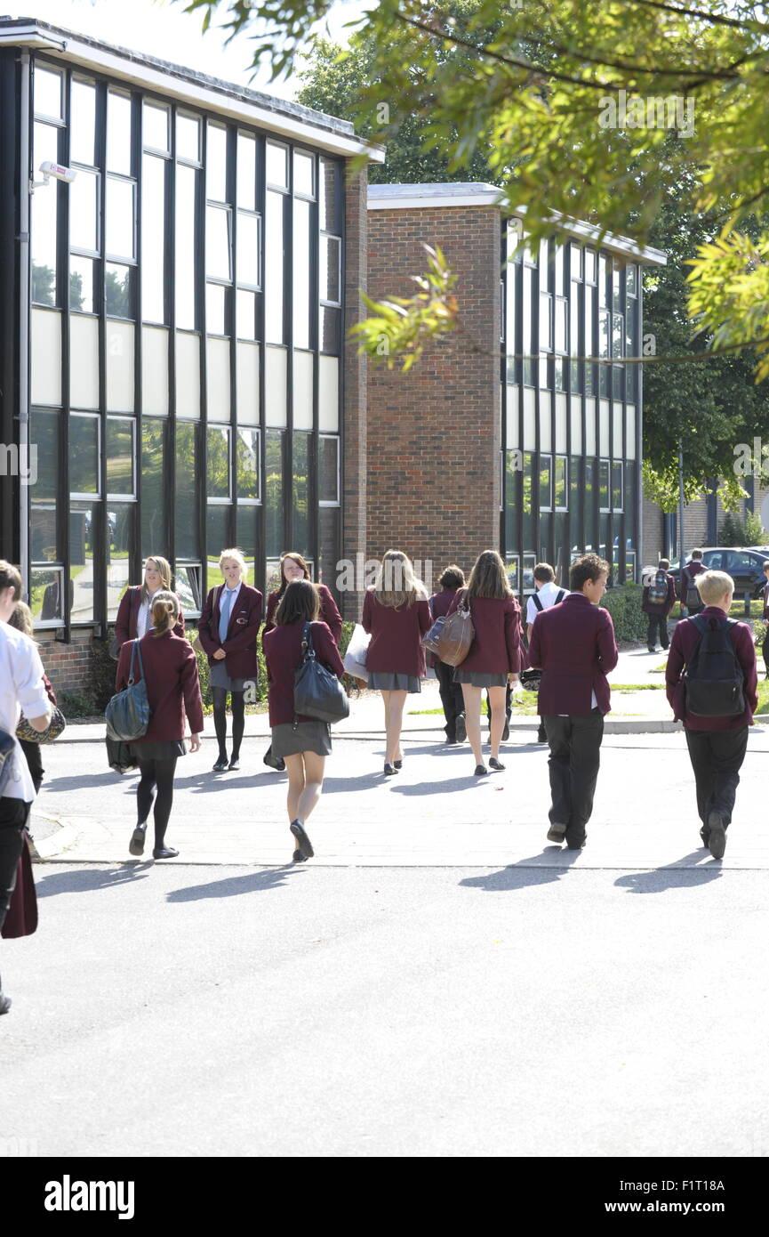 School children walking between school buildings in the sunshine - Stock Image