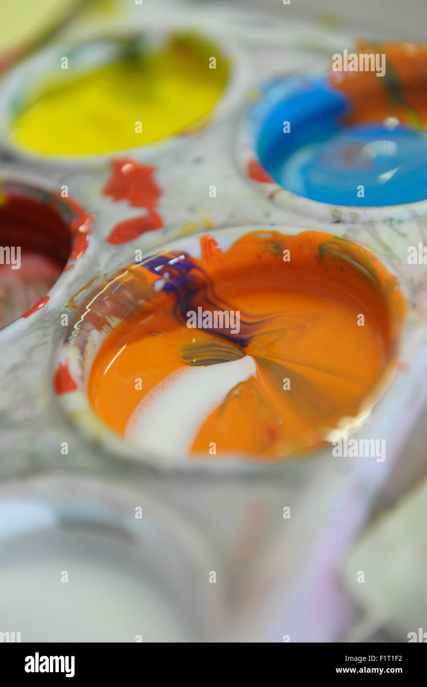 Orange and white gouache liquid paint in a pallette - Stock Image