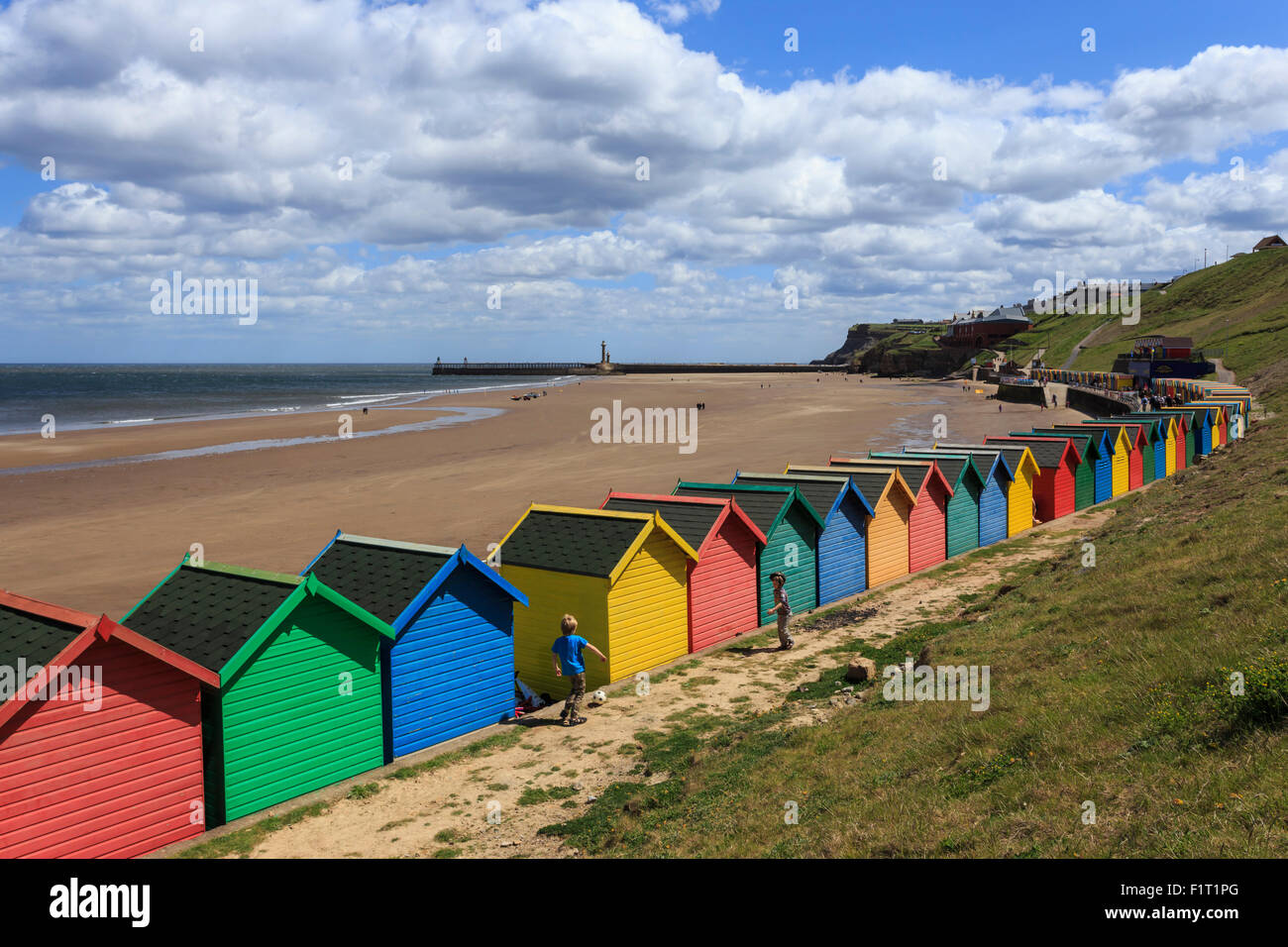 Children kick football near colourful beach huts above West Cliff Beach, Whitby, North Yorkshire, England, United - Stock Image