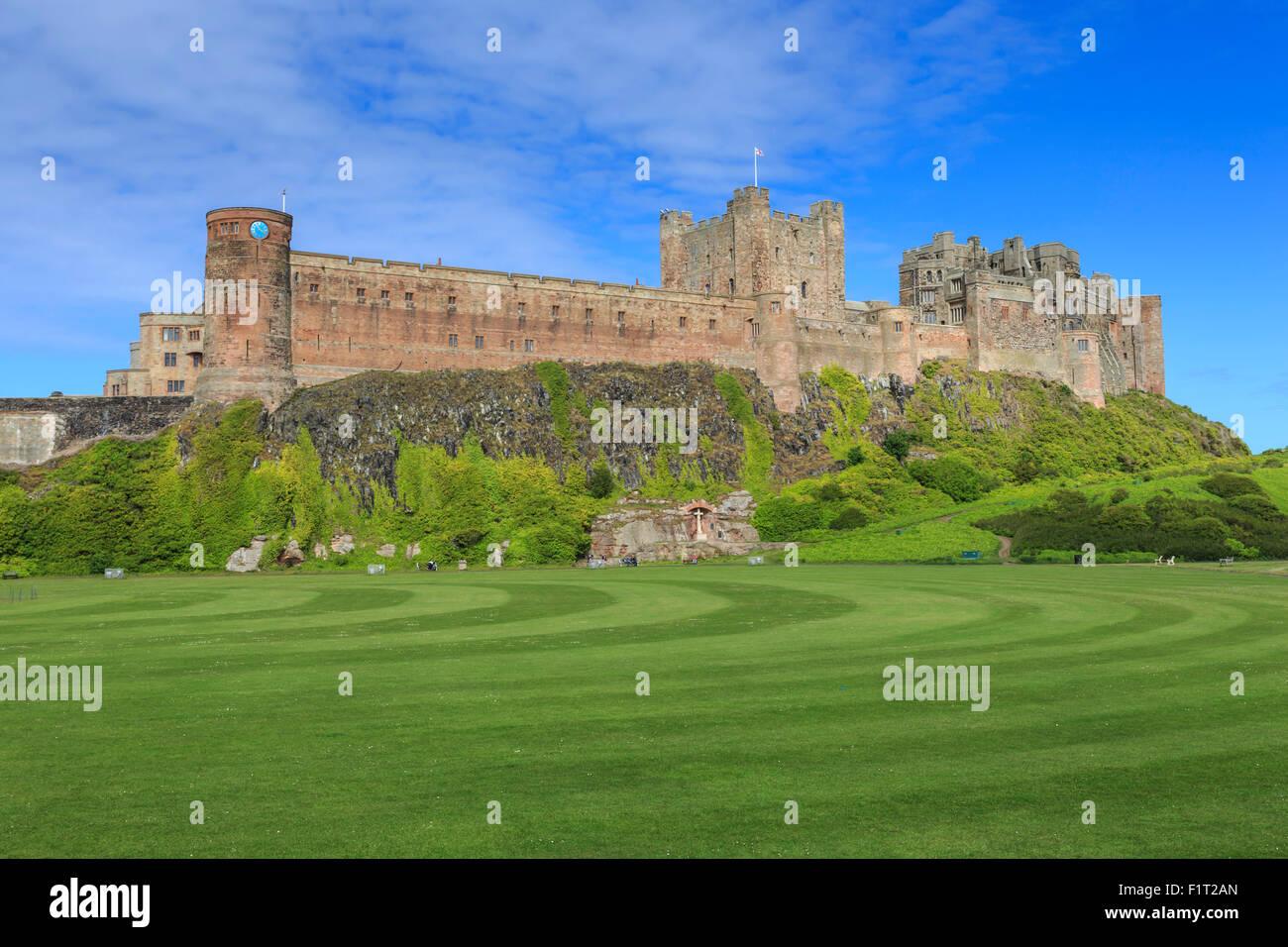 Bamburgh Castle under a blue summer sky, Bamburgh, Northumberland, England, United Kingdom, Europe - Stock Image