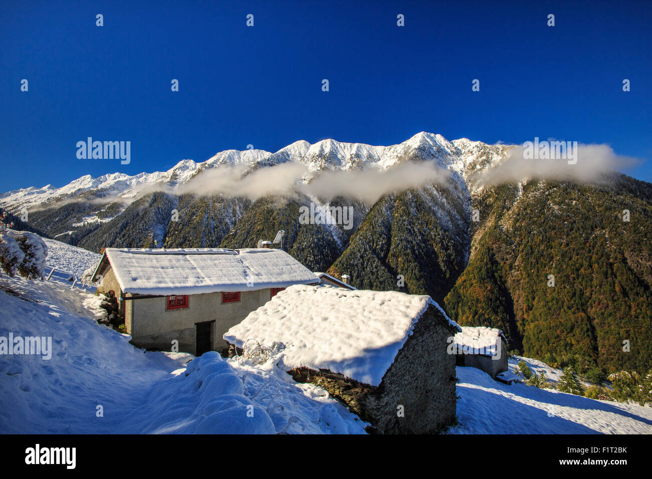Mountain houses framed by snowy peaks, San Salvatore, Livrio Valley ...