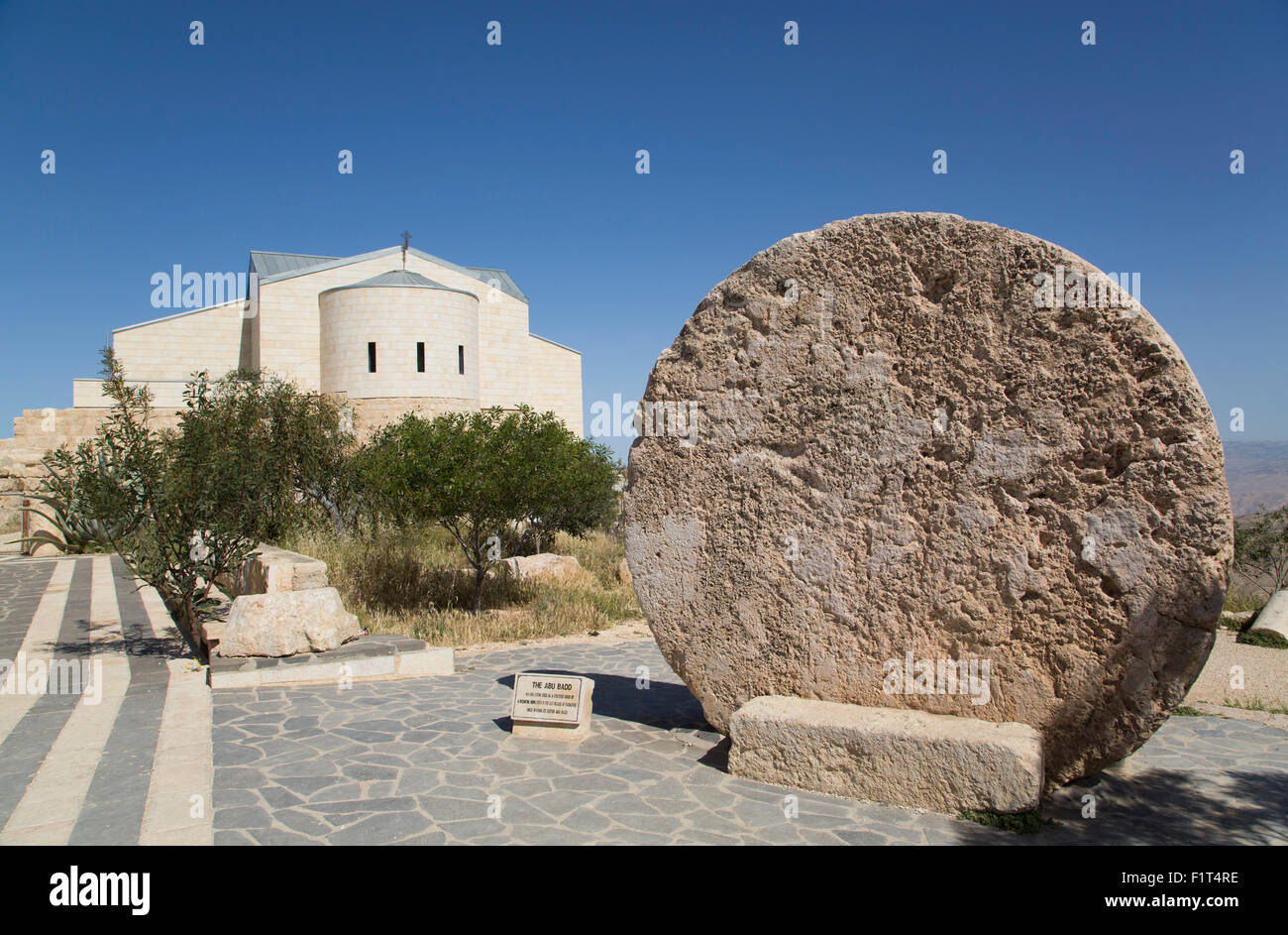 Abu Badd, a rolling stone used to fortify a door, Moses Memorial Church in the background, Mount Nebo, Jordan, Middle - Stock Image