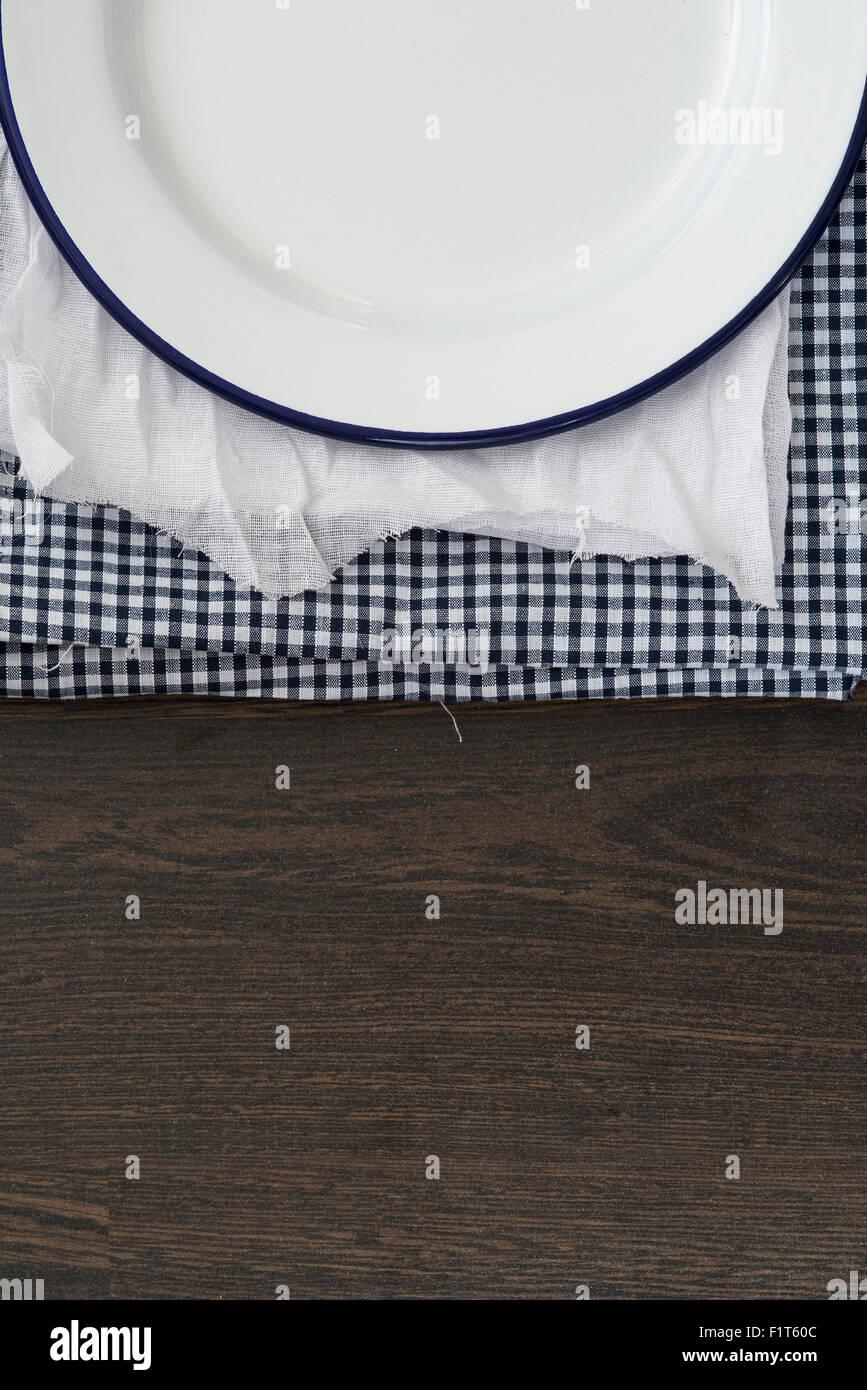 Vintage enamelware crockery on cloths on wooden background - Stock Image