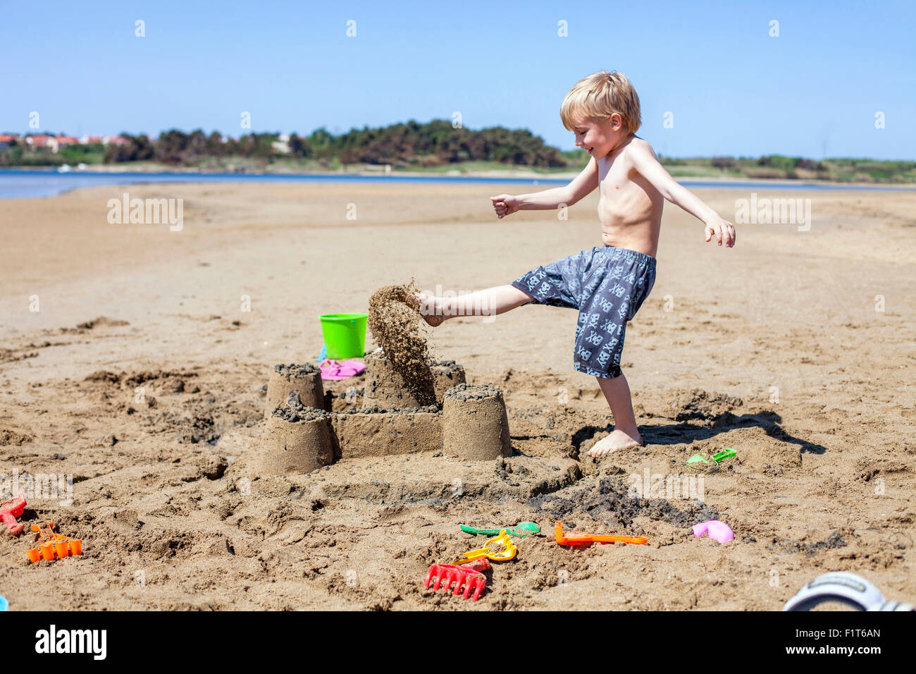 Boy kicking against sandcastle on beach - Stock Image