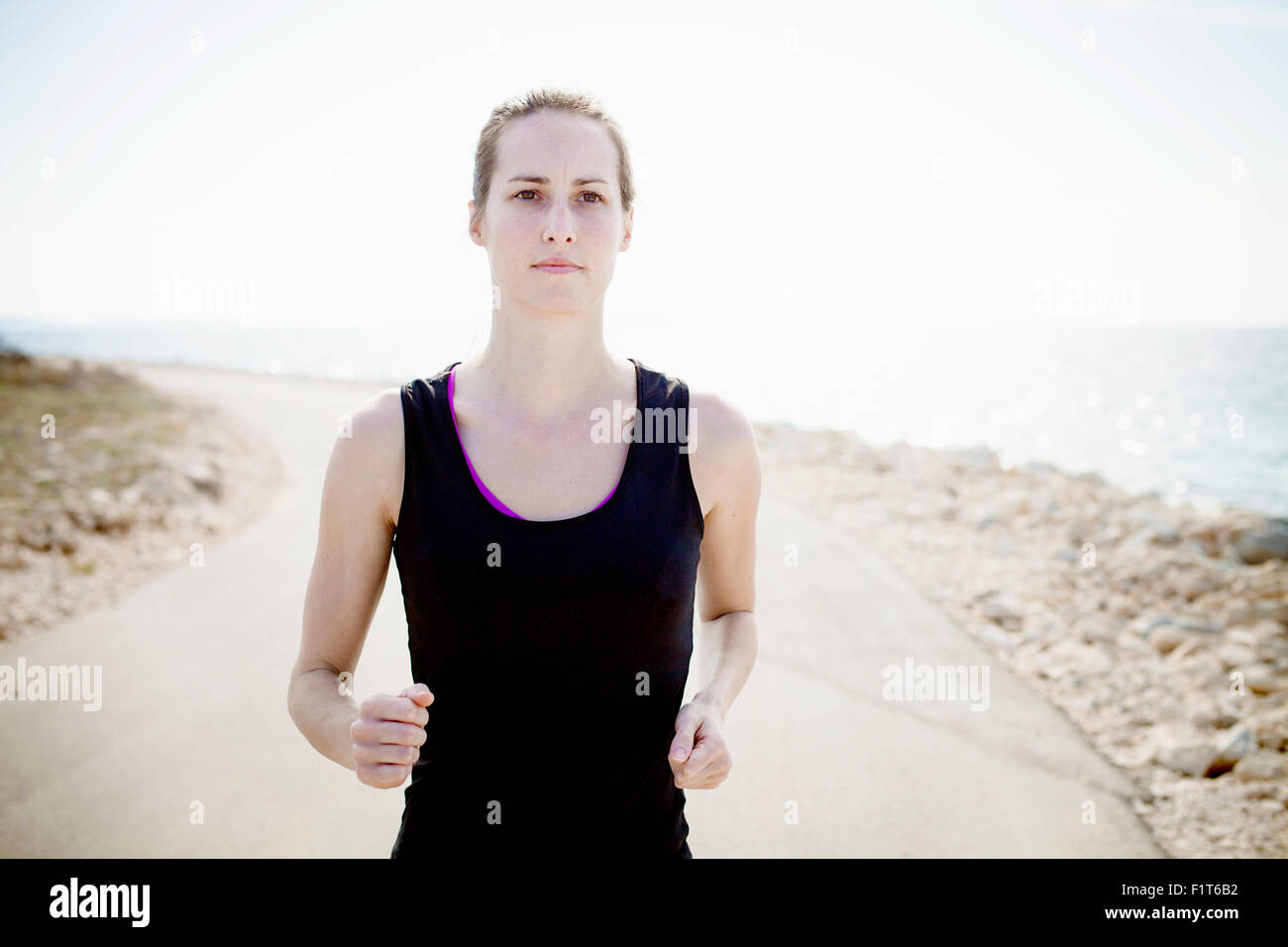 Woman in sports clothing  jogging on waterfront path Stock Photo