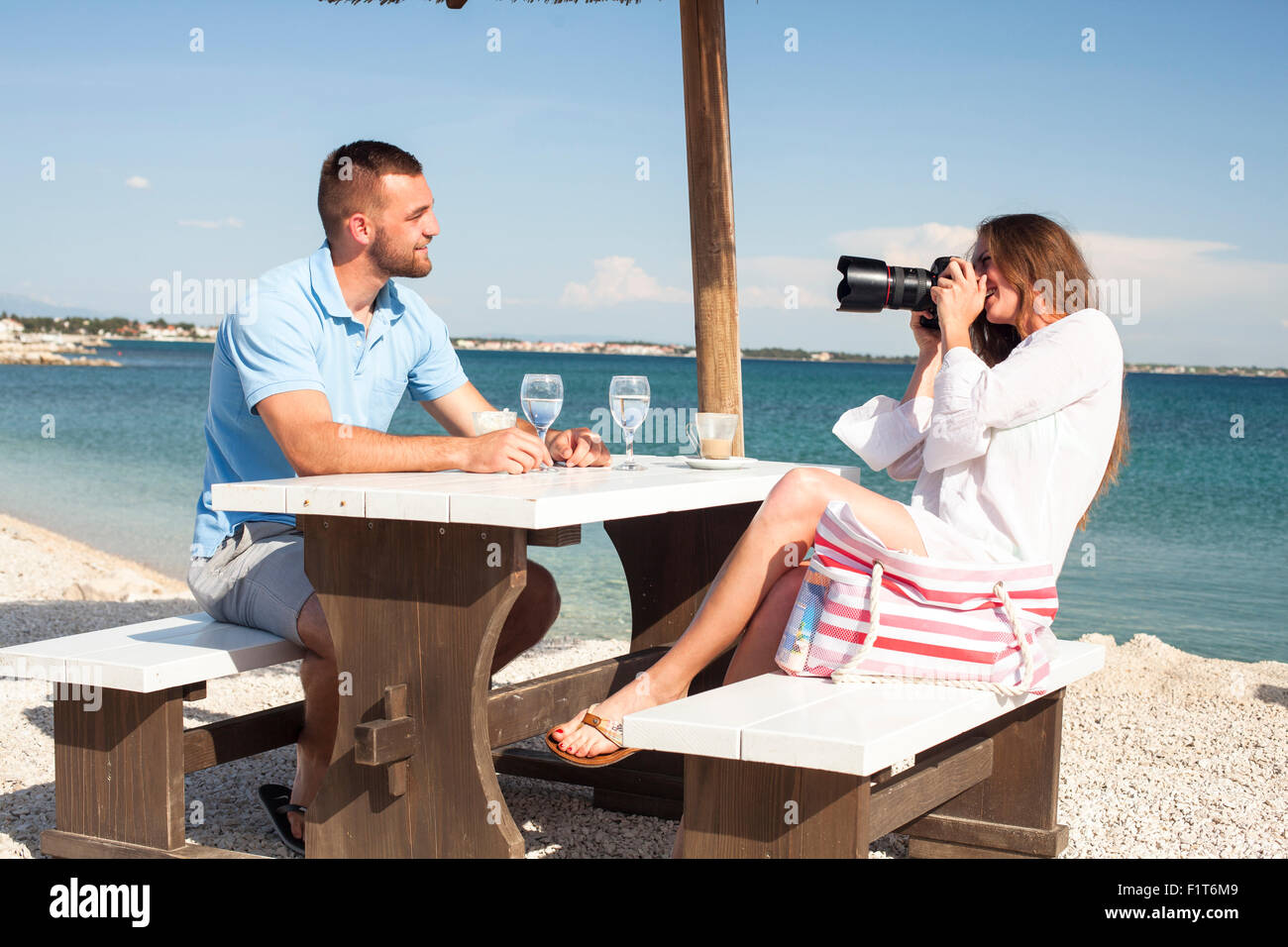 Young woman at beach bar taking photos of friend - Stock Image