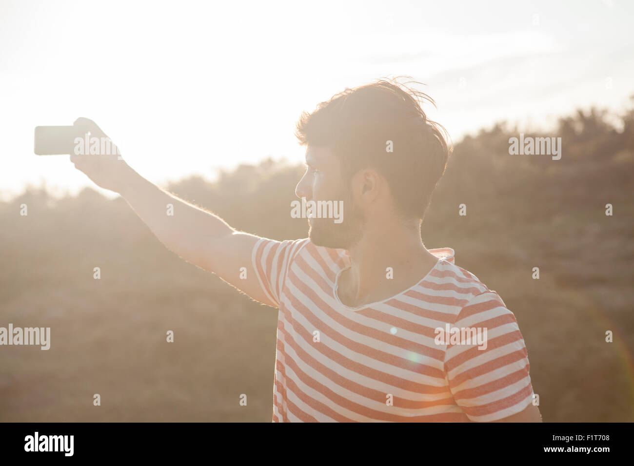 Young man taking photo with smart phone - Stock Image