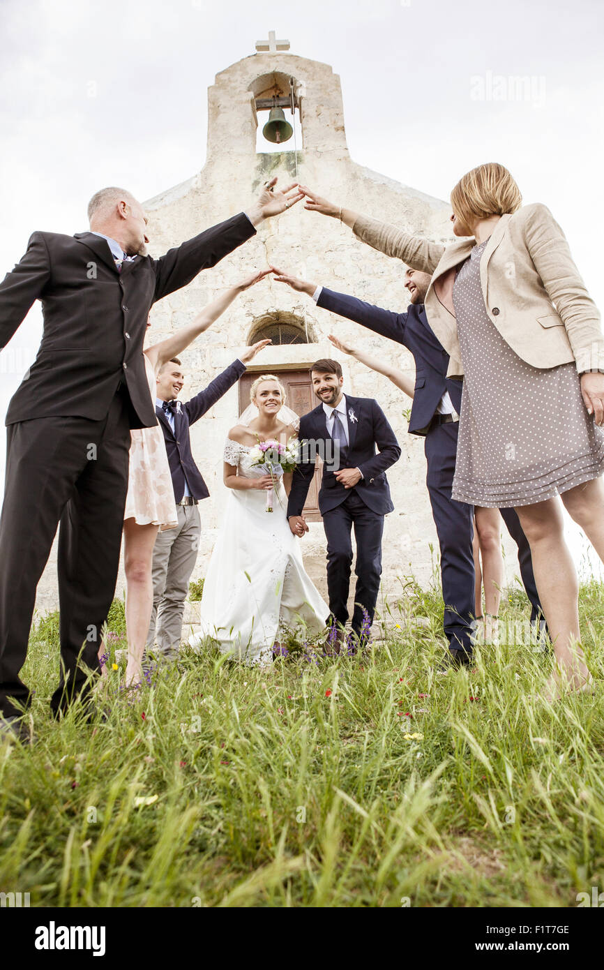Newly wed couple leaves chapel surrounded by wedding guests - Stock Image
