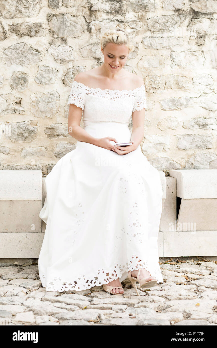 Happy bride in white wedding dress text messaging - Stock Image