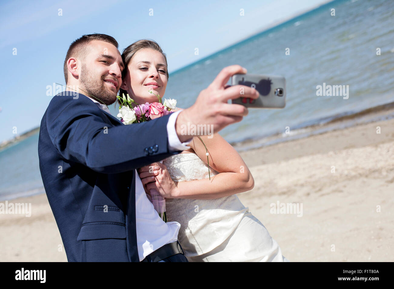Bride and groom taking photo of themselves - Stock Image