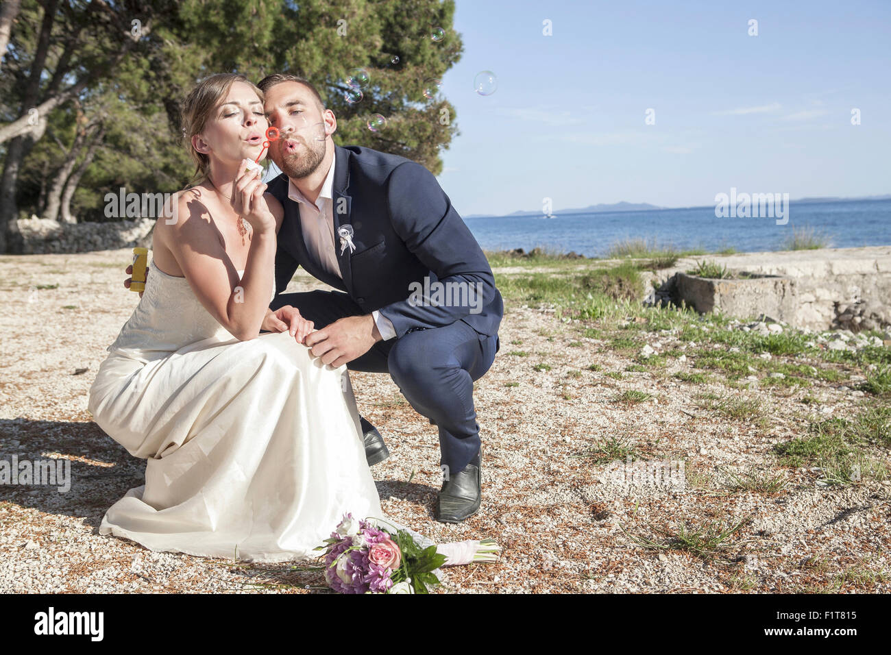 Bride and bridegroom on beach blowing soap bubbles - Stock Image