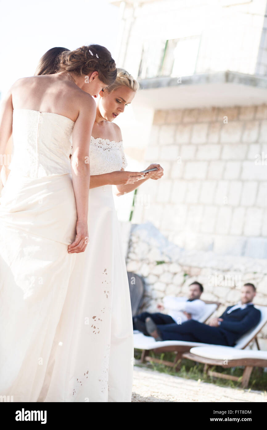 Bride and bridesmaids text messaging outdoors - Stock Image
