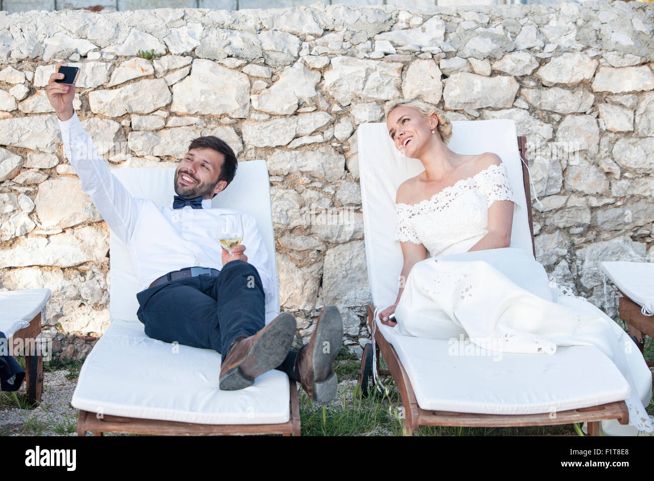 Bridegroom and bride taking photo of themselves - Stock Image