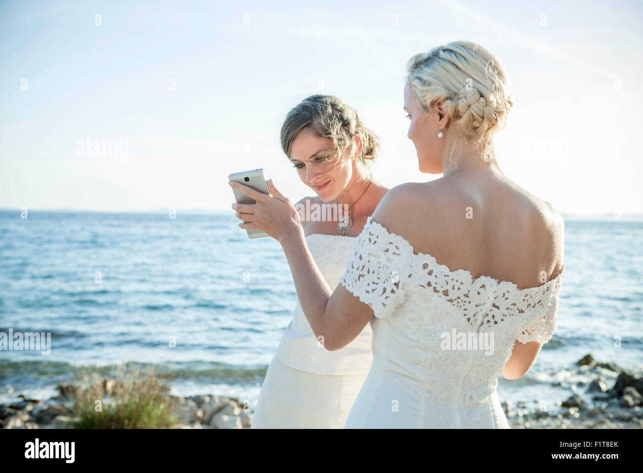 Bride and bridesmaid text messaging outdoors - Stock Image