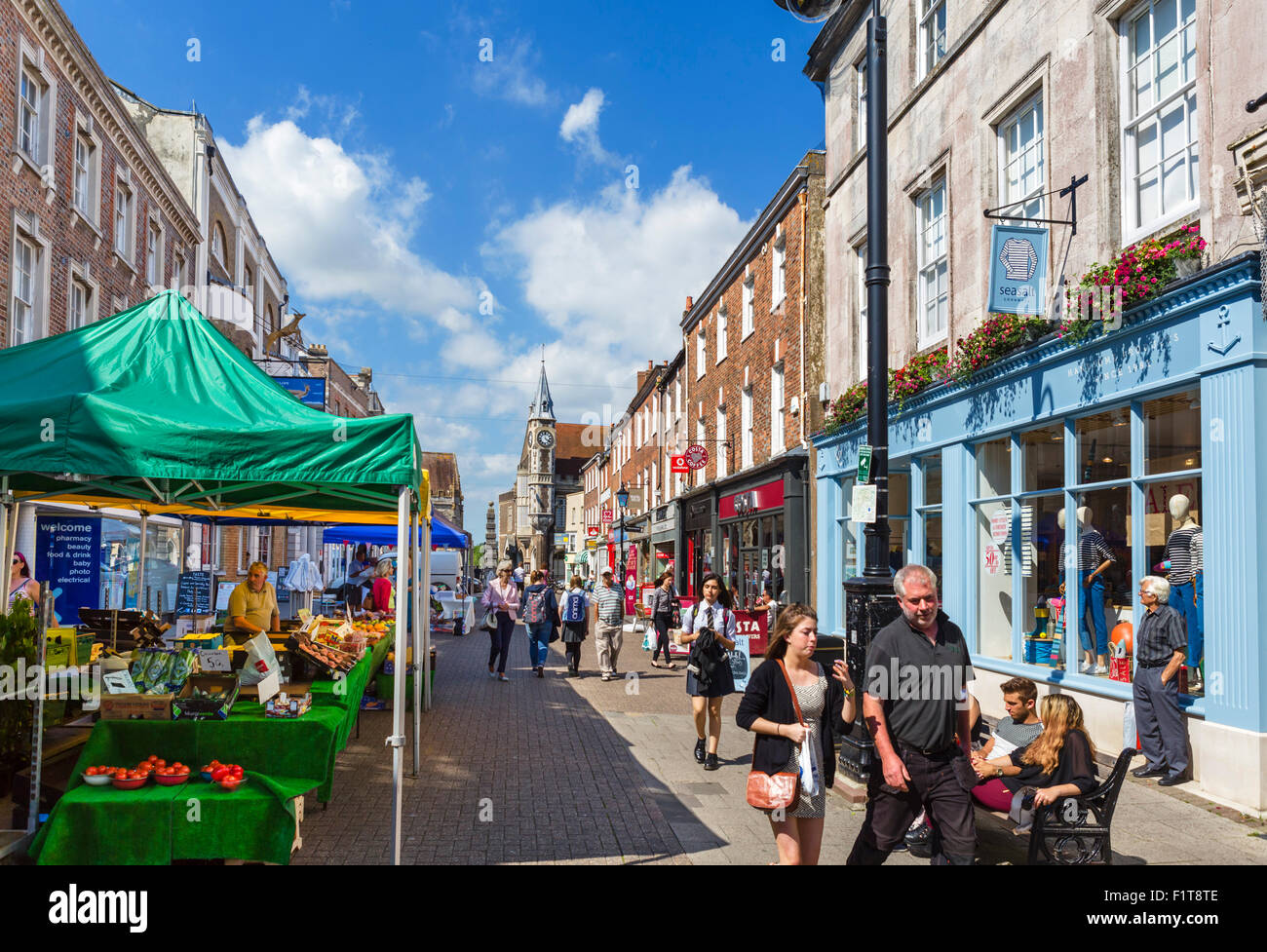Shops and market stalls on Cornhill in the town centre, Dorchester, Dorset, England, UK - Stock Image
