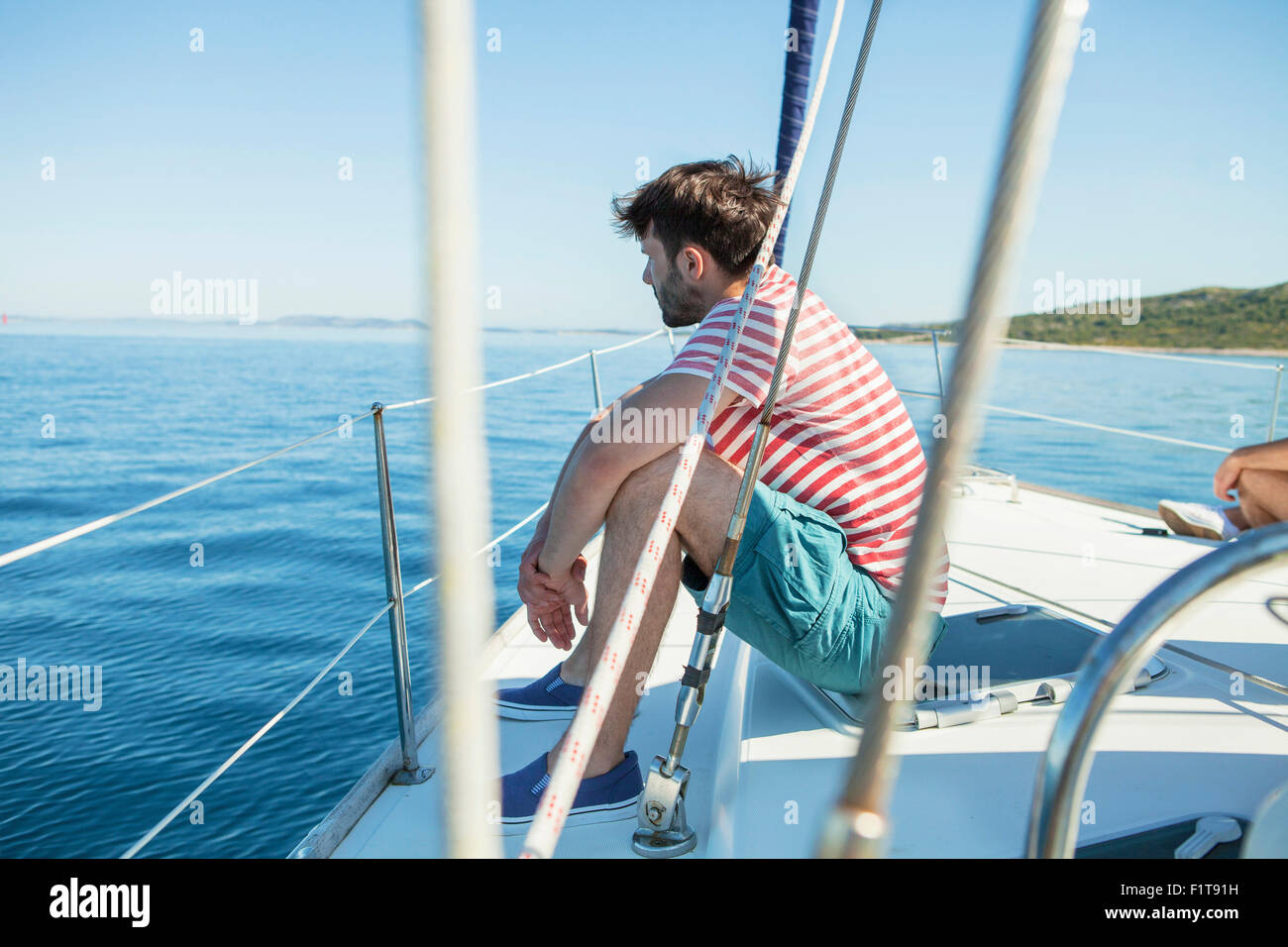 Young man overlooking seascape  on sailboat, Adriatic Sea - Stock Image