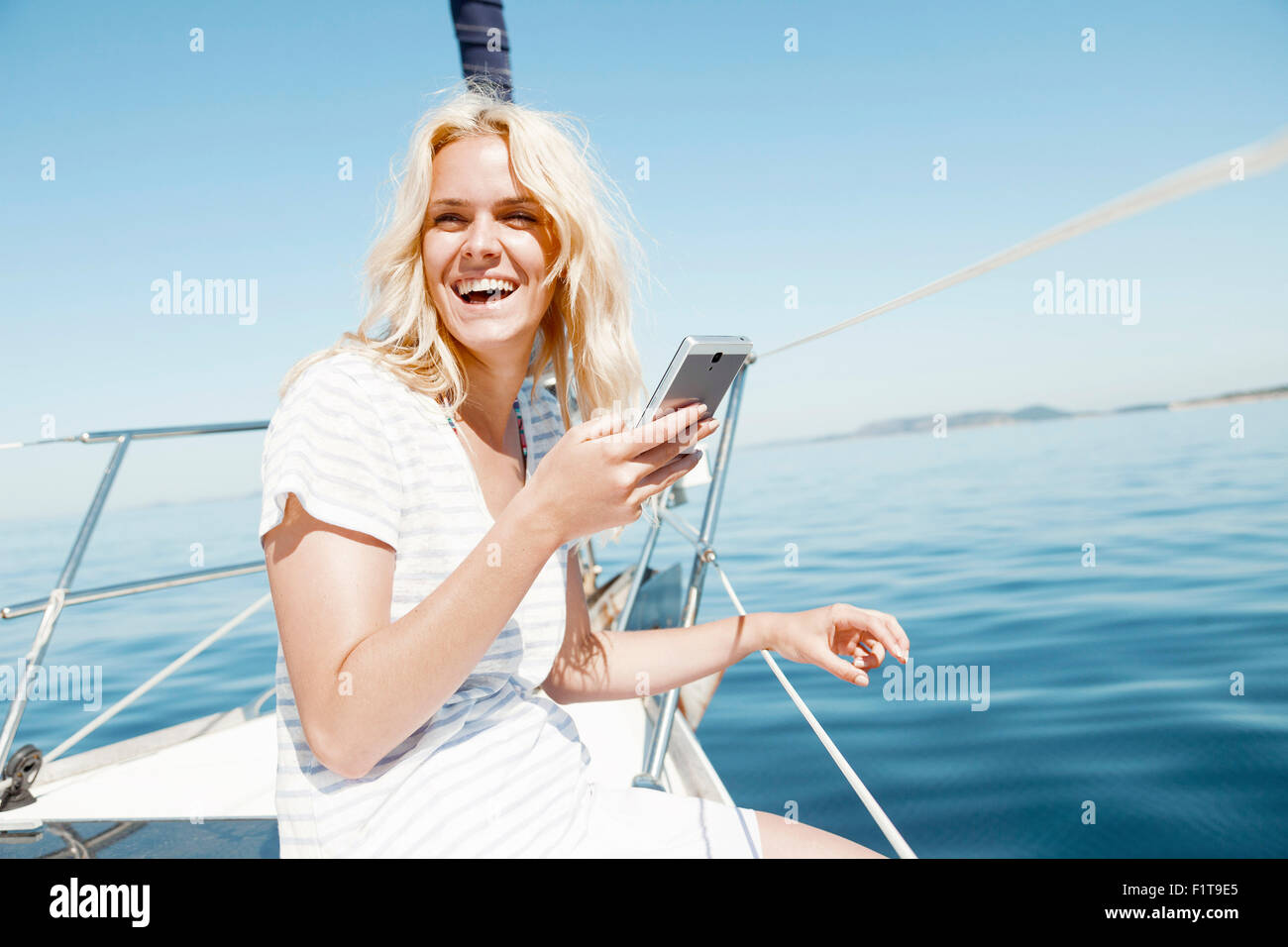 Young woman using smart phone on sailboat, Adriatic Sea - Stock Image