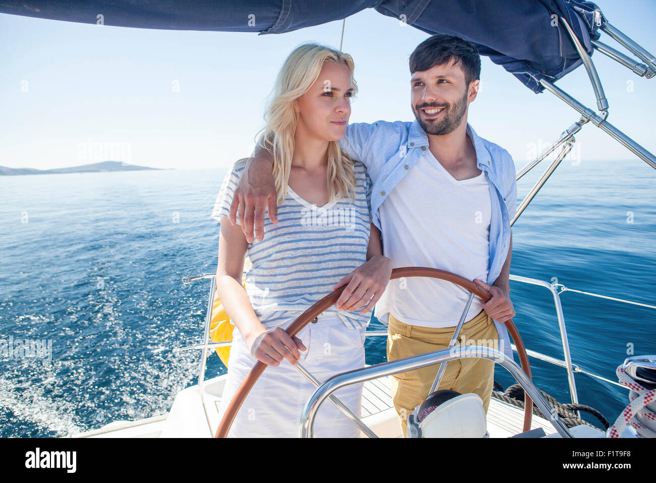 Young couple steering together on sailboat, Adriatic Sea - Stock Image
