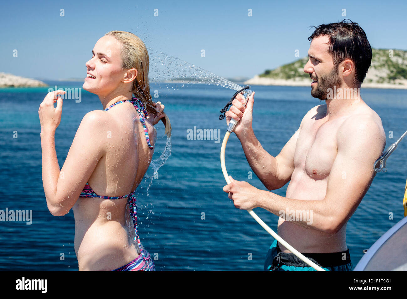 Woman being sprayed with water on sailboat, Adriatic Sea - Stock Image