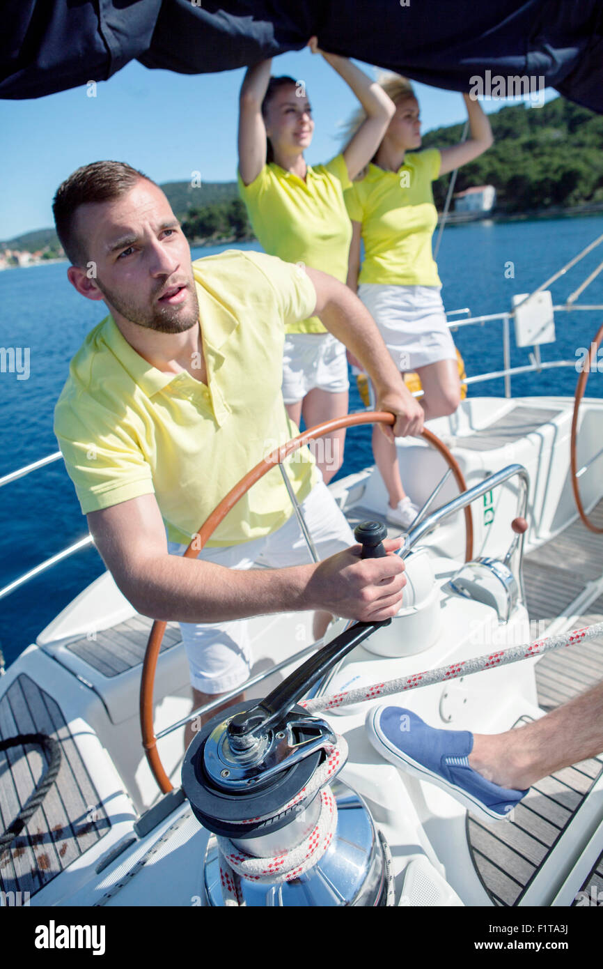 Men steering sailboat, Adriatic Sea - Stock Image