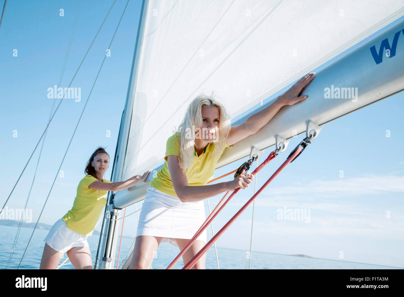Two women adjusting rigging together on sailboat, Adriatic Sea - Stock Image