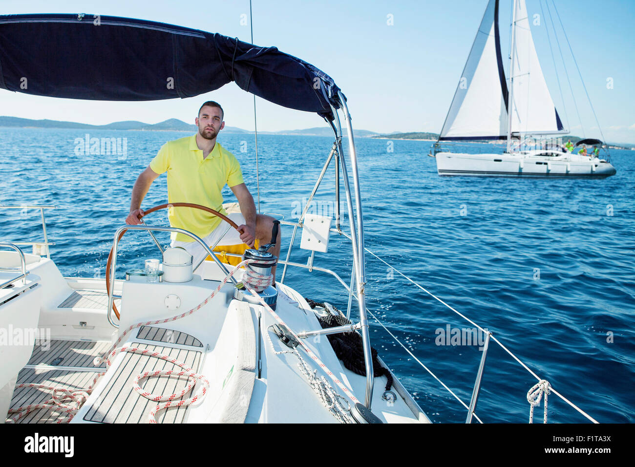Young man steering sailboat, Adriatic Sea - Stock Image