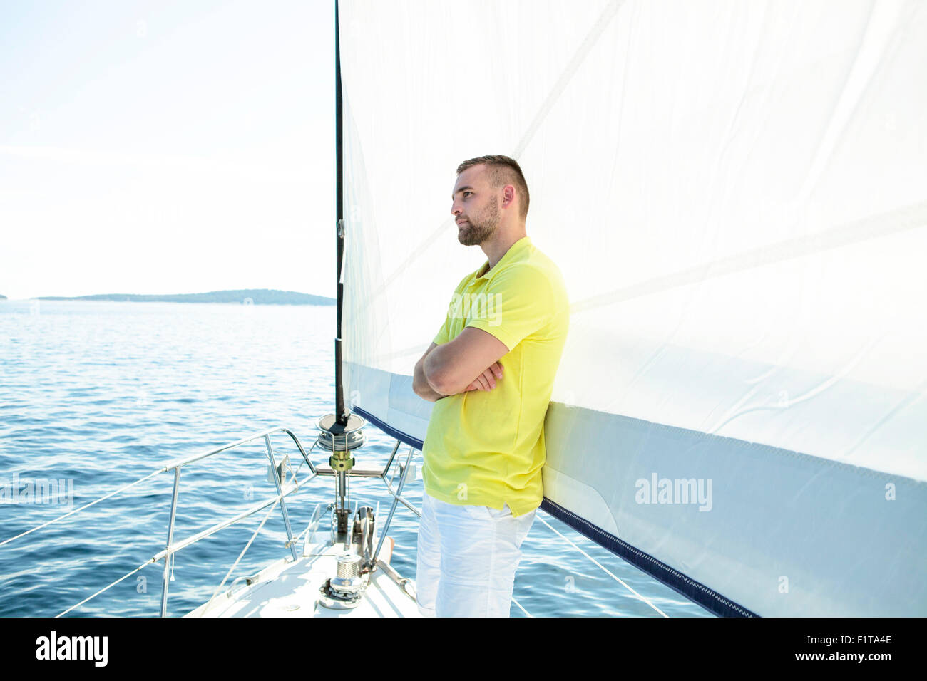 Man standing arms crossed on sailboat, Adriatic Sea - Stock Image