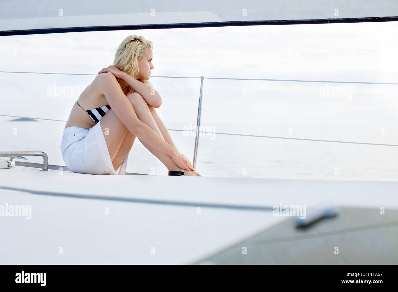 Young woman day dreaming on sailboat, Adriatic Sea - Stock Image