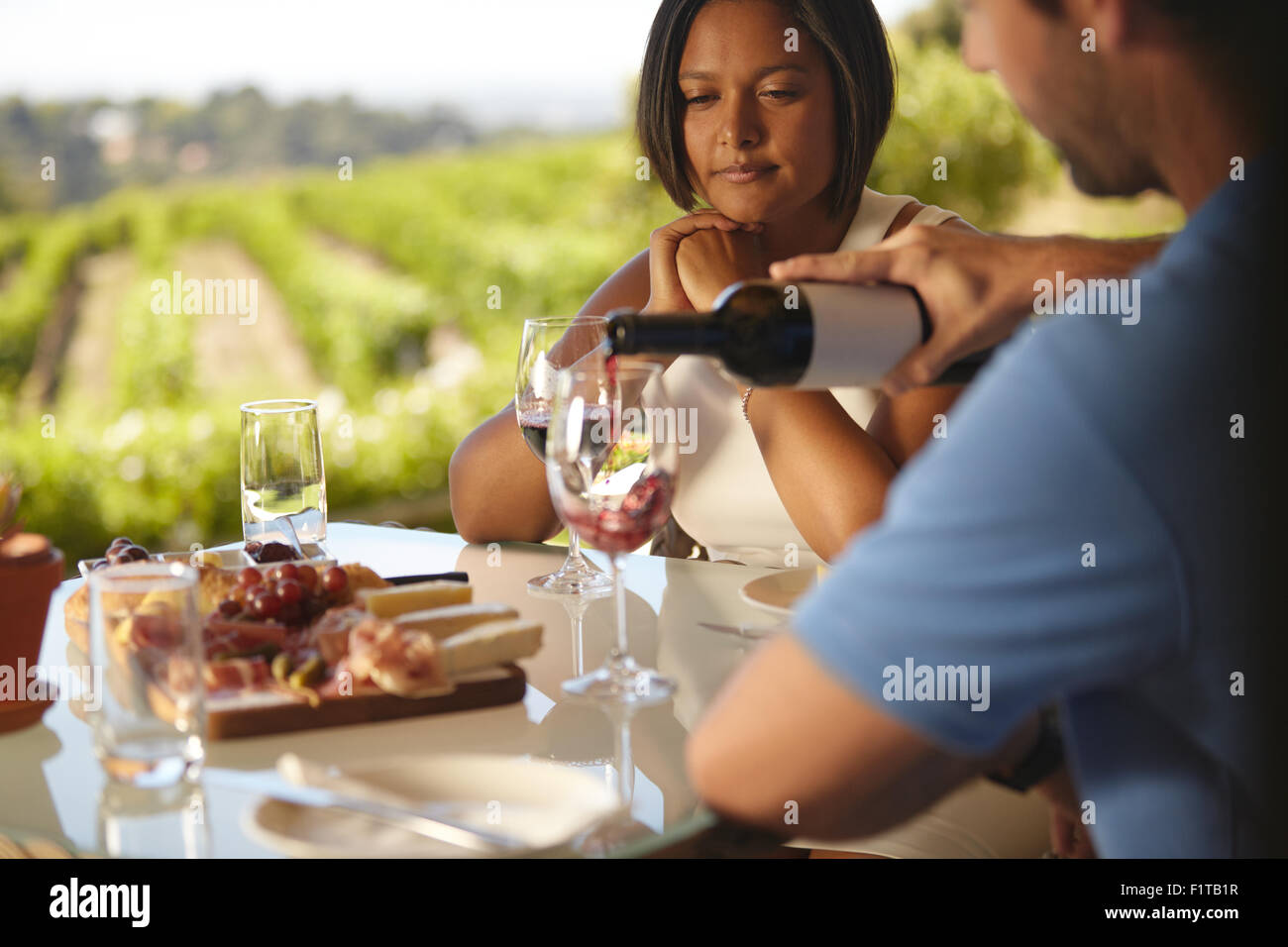 Young woman sitting at a table while man pouring some red wine into his glass. Couple at winery restaurant drinking - Stock Image
