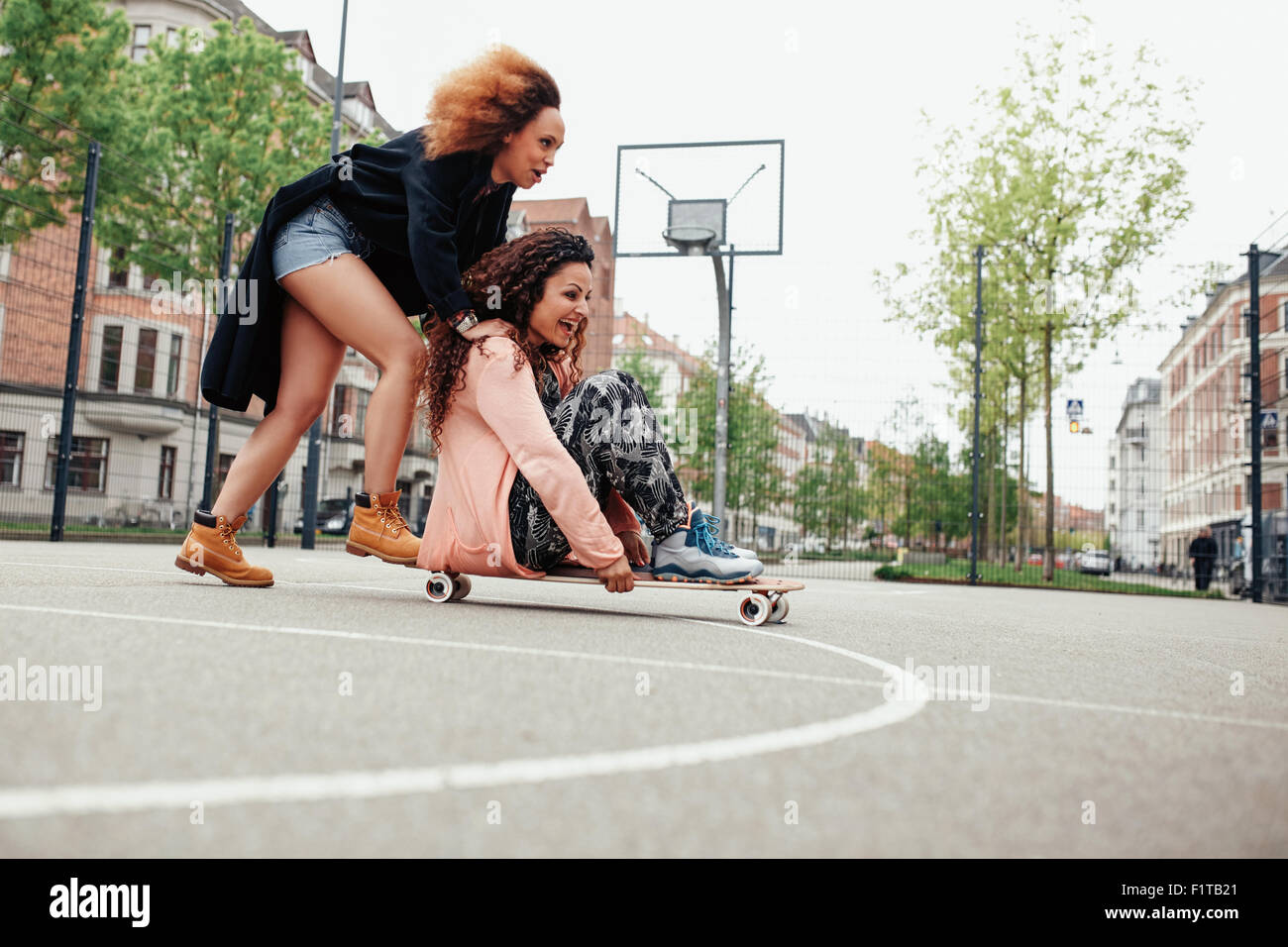 Woman pushing her friend on skateboard. Young women having fun together outdoors. - Stock Image