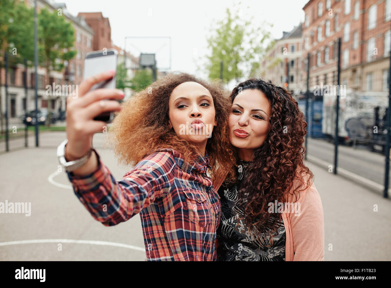 Happy young girls pout and pose for a selfie. Young girl friends taking a self portrait using mobile phone, outdoors - Stock Image