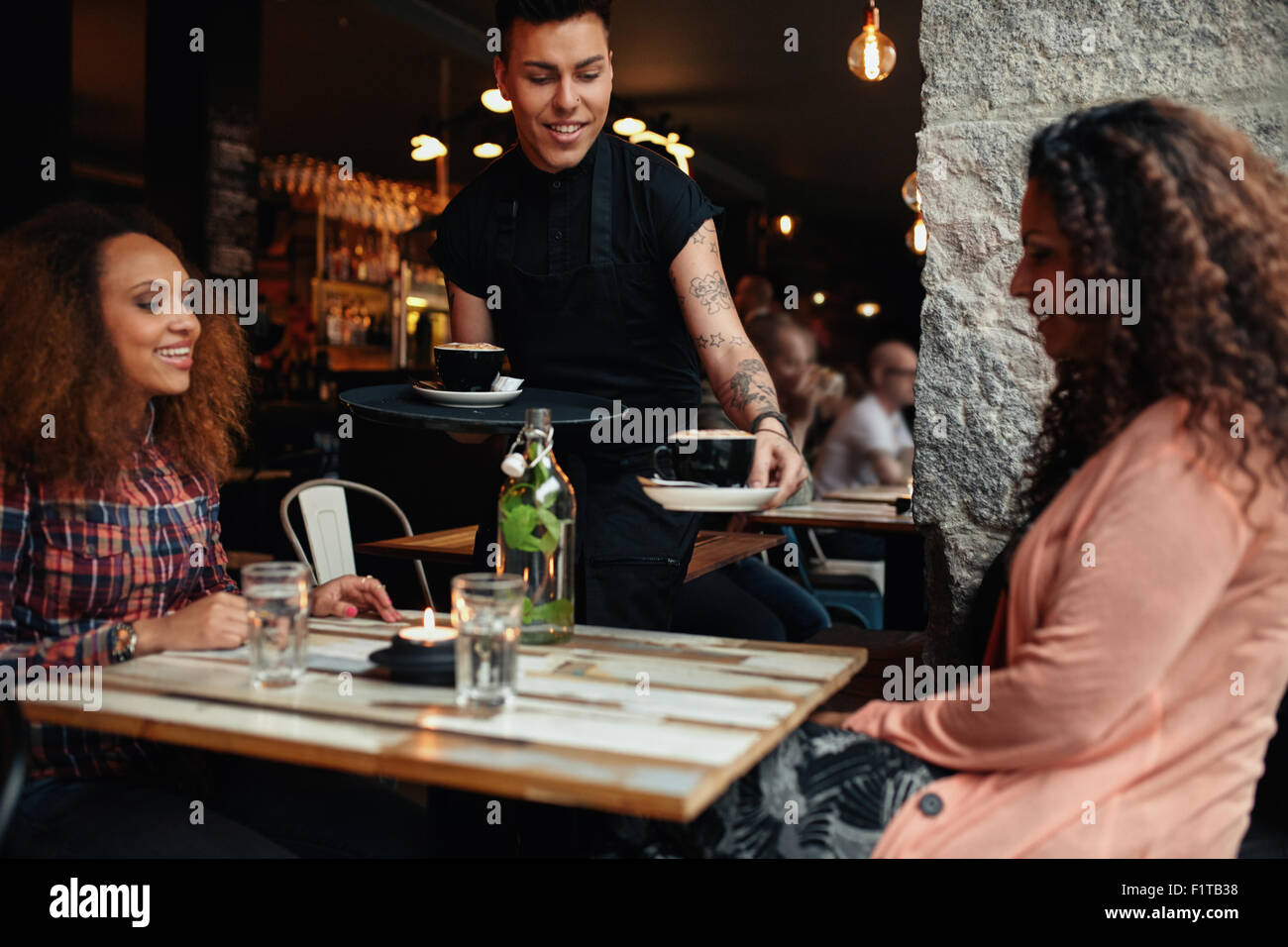 Waiter serving coffee to young women at restaurant. Two female friends at coffee shop. - Stock Image